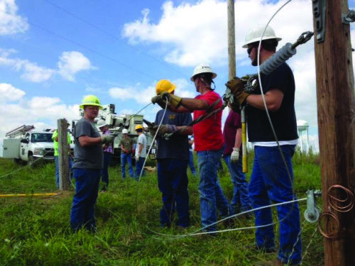 High school FFA students Jeremy Jolly, Seth Ramey, and John Johnson explore career options while working on a simulated line construction with lineman Joey Porter. Photo: Bobby Pease
